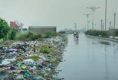 Huisvuil op kant van de weg in ontwikkelingsland op een regenachtige dag stock afbeeldingen