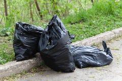 Huisvuil in zwarte plastic zakken, schoonmakende straten royalty-vrije stock foto's