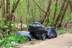 Huisvuil in zwarte plastic zakken, schoonmakende straten royalty-vrije stock afbeelding
