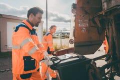 Huisvuilman en vrouwen die vuilnisbakken schoonmaken in afvalvrachtwagen royalty-vrije stock fotografie