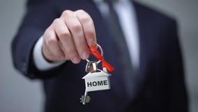 Huiswoord op keychain in zakenmanhand, huisaankoop, de huurdiensten stock footage