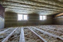 Huiszolder in aanbouw Mansard muren en plafondisolatie met rotswol Het materiaal van de glasvezelisolatie in houten fram stock fotografie