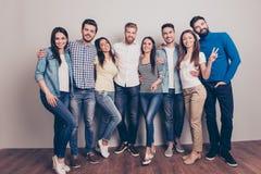 Huit amis heureux posent près du mur, du sourire et du gestur images stock