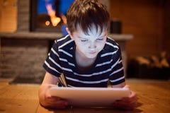 Huit années de garçon à l'aide du comprimé numérique Images libres de droits