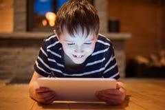 Huit années de garçon à l'aide du comprimé numérique Photographie stock libre de droits