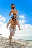 Huit années de garçon s'asseyant sur le ` s de papa épaule Chacun des deux dans des shorts et des lunettes de soleil de natation, Image libre de droits