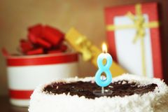 Huit ans d'anniversaire Gâteau avec la bougie et les cadeaux brûlants Photo stock