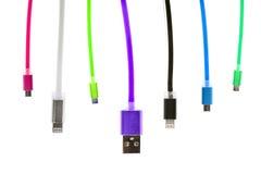 Huit câbles multicolores d'usb, avec des connecteurs pour le micro et pour l'iphone ou l'ipad, accrochent verticalement, sur un f Photographie stock libre de droits