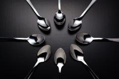 Huit cuillères d'acier inoxydable sur le fond noir photo stock