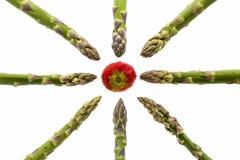 Huit lances d'asperge se dirigeant à une fraise Images stock
