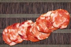 Huit tranches de salami de porc réglées sur l'endroit entrelacé rustique Mat Rough Grunge Surface de parchemin de vintage Photographie stock libre de droits