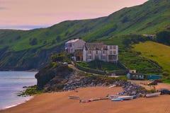 Huizen bij de kust met klippen dicht bij de vuurtoren van Beginpunt, Devon, Engeland royalty-vrije stock afbeeldingen
