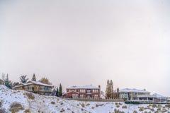 Huizen bovenop heuvel die met sneeuw in de winter wordt bedekt royalty-vrije stock afbeeldingen