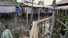 Huizen in de Filipijnse krottenwijken voor armen Houten bruggen van planken bij het hoogwater Armoede van mensen en families stock videobeelden