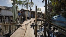 Huizen in de Filipijnse krottenwijken voor armen Houten bruggen van planken bij het hoogwater Armoede van mensen en families stock footage