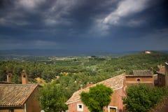 Huizen en bomen in de Provence, met donkere, stormachtige hemel Stock Afbeelding
