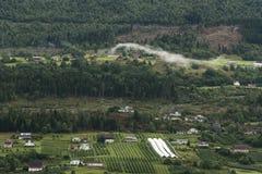 Huizen, Landbouwbedrijven en bomen naast Nordfjord op de manier aan Olden Noorwegen royalty-vrije stock foto