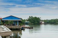 Huizen langs de rivier met lange staartboten in Thailand Royalty-vrije Stock Afbeeldingen