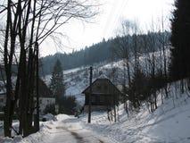 Huizen langs de weg in de winter met sneeuw Stock Foto