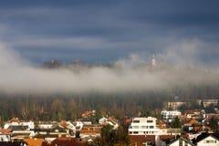 Huizen met betegelde daken op de berghelling, Kerk op de heuvel, reisconcept Zonneschijn in Ljubljana, Slovenië stock foto's