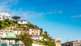 Huizen op een klippenheuvel, op een rots onder groene installaties, interes Royalty-vrije Stock Foto