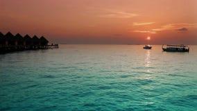 Huizen over het overzees bij zonsopgang maldives stock footage