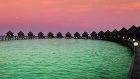 Huizen over het overzees bij zonsopgang maldives stock videobeelden