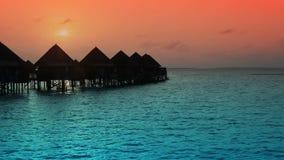 Huizen over het transparante stille zeewater op een zonsondergang stock videobeelden