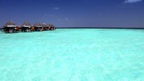 Huizen over transparant stil overzees water tropisch paradijs, de Maldiven stock videobeelden