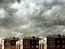 Huizen tegen donkere wolken stock fotografie