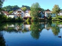 Huizen tegen een vijver in Peiting, Duitsland worden gelegd dat Stock Foto