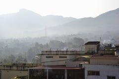 Huizen tegen toneelmening van bergenwaaier in nevel stock foto