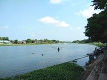 Huizen, tuin op rivieroever, boot in rivier bij landelijk in Thailand royalty-vrije stock afbeelding