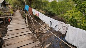 Huizen van de armen in de Filipijnse krottenwijken Het moeras Houten bruggen van planken bij het hoogwater Kleren op kant stock video