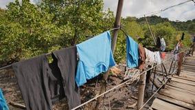 Huizen van de armen in de Filipijnse krottenwijken Het moeras Houten bruggen van planken bij het hoogwater Kleren op kant stock videobeelden