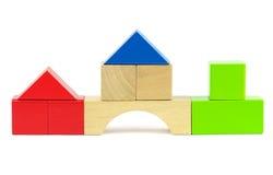 Huizen van stuk speelgoed houten kleurrijke bouwstenen worden gemaakt die Stock Foto