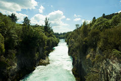 Huka Falls in New Zealand. The great view from the Huka Falls trail in New Zealand. the energetic blue sky with the ice blue water and the lush green plants Royalty Free Stock Photo