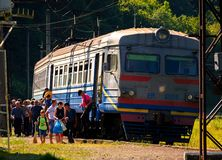 Ancient electric train arrival. Huklyvyi, Ukraine - 20 Jul, 2017: ancient electric train arrival. people quickly take off royalty free stock images