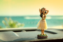 Hula dancer doll on Hawaii car road trip. Doll dancing on the dashboard in front of the ocean. Tourism and Hawaiian travel freedom concept