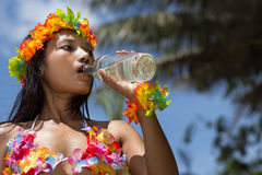Hula Hawaii dancer drinks from bottle stock images