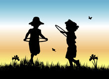Hula Hoop Girls. Silhouette of two young girls skipping with hula hoops in the grass Royalty Free Stock Photography