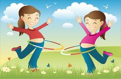 Hula hoop twins. Twins playing hula hoop in the park Royalty Free Stock Photography