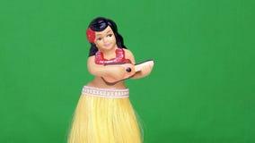 Hula-Mädchen-Puppe gegen grünen Schirm Stockbild