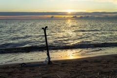 Hulajnoga na piaskowatej plaży na plaży przy zmierzchem obraz royalty free
