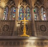 HULL, UK - 3RD MARCH 2019: A yellow painted crucifix sits in front of stained glass in the Hull Minster stock photography
