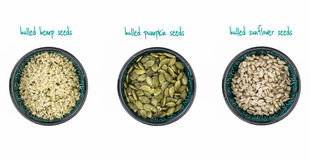 Hulled hemp, pumpkin and sunflower seeds in bowls royalty free stock photos