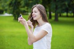 Hulp dichte omhooggaand van de lippenstift mooie jonge donkerbruine vrouw Royalty-vrije Stock Foto's