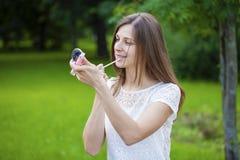 Hulp dichte omhooggaand van de lippenstift mooie jonge donkerbruine vrouw Royalty-vrije Stock Afbeeldingen