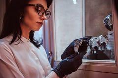 Hulp dragende handschoenen die de horloges van exclusieve mensen in de opslag van luxejuwelen houden royalty-vrije stock foto's