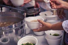 Hulp met voedende dakloze mensen om honger te verminderen Armoedeconcept stock foto